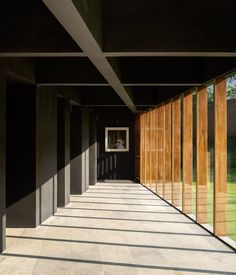 An angled wall runs along one side of the bedroom volume so each room gradually increases in size. The unusual shape also creates a triangular hallway outside the bedrooms that is flanked by windows with wooden frames offering views of the garden. Stone Deck, Outdoor Walkway, Indoor Outdoor, Basement Floor Plans, Weekend House, Huge Windows, Tree Canopy, Ground Floor Plan, Black Walls