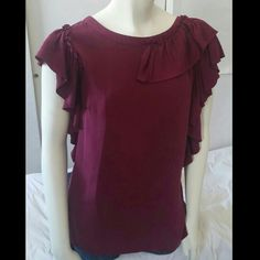 """Ann Taylor Top 91% silk, 9% spandex. Very unique. Color matches first picture the best. Varies in color depending on lighting. Wider arm hole openings covered by ruffles. Neckline has ruffle on half in the front and continues to cover half of the back. Measures 19"""" across bust, 25.5"""" from shoulder to bottom. Measurements taken laying flat Color is a plum/burgandy. Dry clean only Ann Taylor Tops"""