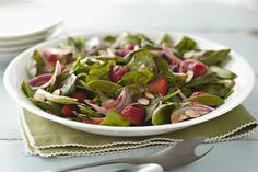 Fresh spinach is tossed with snap peas, juicy strawberries, onions and toasted nuts.  Topped off with a drizzle of tangy dressing, this salad makes a super, seasonal side.