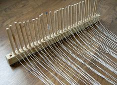 Peg weaving  Peg weaving involves winding the weft fabric around the sticks in a back and forth motion until you have completed enough rows to fill the pegs.  The pegs are then removed from their holes, pulled up and over the weaving and replaced as the weft slides down over the warp strings.    The beauty of this system is that the weaving holds a consistent tension and does not pull in or narrow at the centre of the work