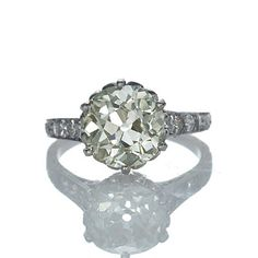 tunning Edwardian engagement ring. A gorgeous Old Mine cushion cut diamond weighing 3.05 cts and certified by the GIA as UV color and VS2 clarity (Report #1142947032) has an enchanting pale yellow hue and phenomenal sparkle. Set with 6 round diamonds and beautifully hand engraved,this wonderful ring is a treasure from a bygone era. Platinum.