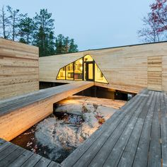 Cedar wraps around this Ontario lake house by American firm Lazor Office, which comprises two volumes that face the water and are joined at their corners.