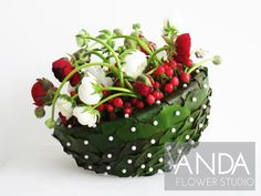 Movement and texture created with a bowl of pearl pinned Galax leaves containing white and red Ranunculus and red Hypericum berries.
