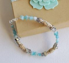 """Bead-bracelet  """"Here is a close up of my bracelet.  To create the beads, I diecut some vintage book pages, which worked well because they were lighter weight, just like the papers in the Beautiful Beads paper packs...they're a bit easier to roll that way, but you can use regular scrapbooking papers too.  I added some aqua glass beads and some other rhinestone beads to create my bracelet.  This was my first attempt at creating any kind of real jewelry and I had a blast with it!"""""""