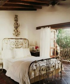 wood beams, iron bed, large ornate wall sconce, tile floors   simple but elegant