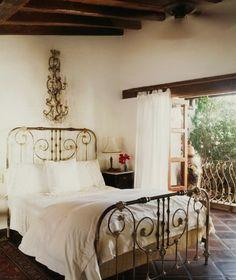 wood beams, iron bed, large ornate wall sconce, tile floors   simple but elegant