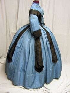 1860's Blue & Black Promenade Ensemble: What a striking color combination. This civil war era dress was beautifully constructed. The bust is 32, the waist is 21, the skirt length in front is 47 and the skirt around the bottom measures 170. The black silk is suppose to line up from the bodice to the skirt.
