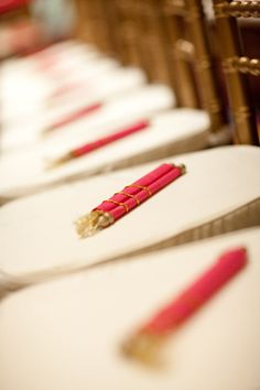 Red and Gold Scrolls on Chiavari Chairs    A closeup of a pink wedding scroll given to all the guests at a Hindu Indian wedding.