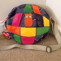 Authentic Oilily handbag in multi color leather Authentic Oilily Italian boutique round purse in leather, navy with multi color patent with summer edition charm attached. Kids bag but nice size purse for all. Oilily Bags