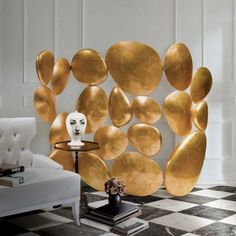 Gold - Folding Screen - Boca Do Lobo. Innovative yet sublime this piece of art was designed in true Boca Do Lobo style. Reminiscent of a group of pebbles forming asculptural like composition at the bottom of a river, this ultra lux screen is fashioned from nineteen pieces offiberglass filled with expandable polyurethane and finished in gold leaf with a high gloss varnish.