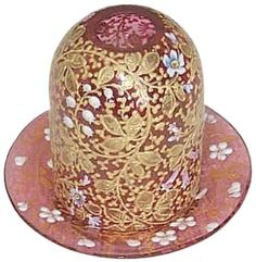 """Fairy Lamp with cranberry dome heavily decorated in gold with white & blue flowers. The dome, slightly smaller than standard pyramid-size, is 2.0""""d. x  2.75""""h. Dome rests on simple saucer base decorated in gold with white flowers. Saucer base is acid-etched in script """"Moser Karlsbad."""""""