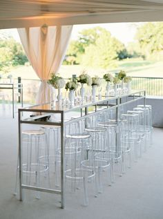 modern elegant tented wedding reception decor | high top community cocktail table surrounded by clear acrylic stools