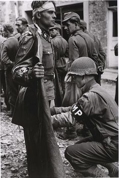 An American military policeman searches a captured German SS soldier, Normandy 1944, by Robert Capa