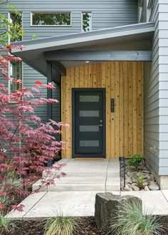 An exotic hardwood wall makes the sleek, black, modern door on this industrial home pop against the gunmetal gray of the exterior. A Japanese maple offers additional color to the front of the home.