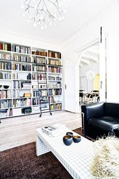 Modern living space with a floor to ceiling wall of books, and a black leather sofa