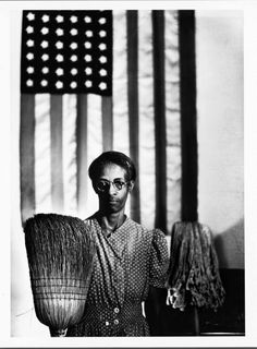 1942: Iconic Gordon Parks image of Ella Watson with broom & mop with American flag