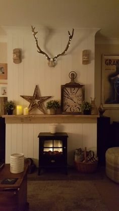 Cosy fireplace, tongue and groove to cover the old horrid firplace.homemade sconces and antlers donated by my gamekeeper nephew.