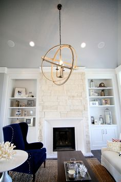 built-in shelving around the white stone fireplace. and love the navy chair with nail heads.