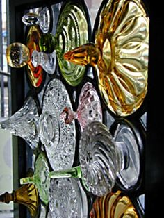 Hanging window composed of serving plates, wine bottle bottoms, stemware bottoms and faceted stained glass jewels.