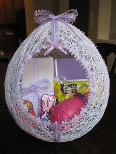 Lacy handmade easter egg basket.  We used to make these when I was little.  Blow up a balloon.  Make paste of flour/water.  Wet some white string or yarn and wrap, wrap, wrap.  When dry, cut out the hole and decorate.    I'm so tempted to try this one.  I think Emma would love it.