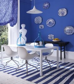 If you find a colour you love - be bold! Here, Egyptian Blue walls work perfectly with the striped rug, while a painted wooden floor and contemporary white furniture keeps it fresh.