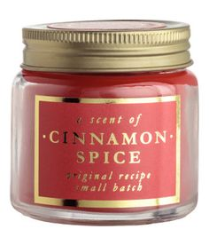 Rød/Cinnamon. Et duftlys i glassbeholder med etikett og skrulokk i metall. Diameter 6 cm, høyde 6 cm. Brennetid 14 timer.