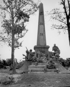 """""""Marines, following the rapid Japanese retreat northward on Okinawa, pause for a moments rest at the base of a Japanese war memorial. They are (on steps) Pfc. F. O. Snowden; Navy Pharmacist's Mate, 2nd class R. Martin; (on monument, left to right) Pvt. J. T. Walton, Pvt. R. T. Ellenberg, Pfc. Clyde Brown, Pvt. Robb Brawner. Photo was taken during the battle for Okinawa."""""""