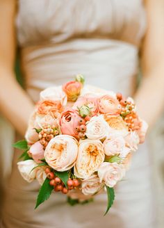 The bridesmaid is holding a beautiful peach color bouquet. Garden rose bouquet