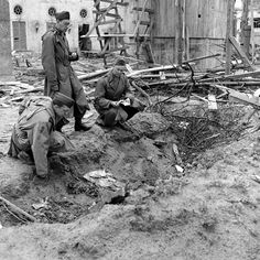 Unpublished. LIFE war correspondent Percy Knauth (left) sifts through dirt and debris in the shallow trench in the garden of the Reich Chancellery where the bodies of Hitler and Eva Braun are believed to have been burned after their suicides. Vandivert's typed notes around this scene include one of the more laconic of the photographer's sometimes-slangy observations of what he witnessed while exploring outside the bunker: