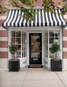 Love the black  & white striped awning over the black door with planters