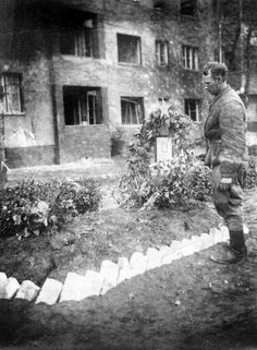 May 1945: Soviet soldier pays his respects at the grave of a comrade in devastated Berlin.  Many Russian KIAs were buried near the location where they fell; in November 1945, the first Soviet military cemetery opened in Berlin to host the remains of 2,500 soldiers buried around the city during the battle.