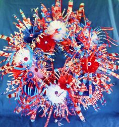 Hi! I just wanted to share this Patriotic Wreath I just finished making. It's a Styrofoam base  I made the fireworks/flowers out of painted water bottles. The centers are made from plastic raffia yarn  my flower loom. I made a few corkscrews of metallic red/blue pipe cleaners  red/white/blue stars wired garland  a few glittered ribbon loop picks to fill in some spaces. To me it looks like a fireworks explosion! :D