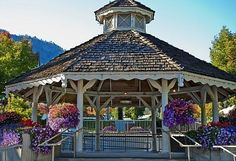 This stunning gazebo is in the late summer with massive flower baskets and leaves beginning to turn for a photo that just invites you to step inside.