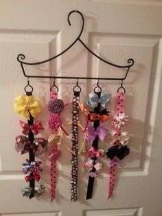 Homemade bow/headband holder. Find a unique hanger - this one was a thicker black metal. Purchase hooks with a circle that will face out when it hangs (usually in any curtain rod section). Find cheap black wire (or other color) in jewelry aisle at craft store. I recommend thin wire that matches your hanging hooks. Buy 7/8 inch ribbon in whatever length you wish. I would place about a 1/2 inch through the hook, fold it over & hot glue it. I also used 2 strips of ribbon to make the headband…