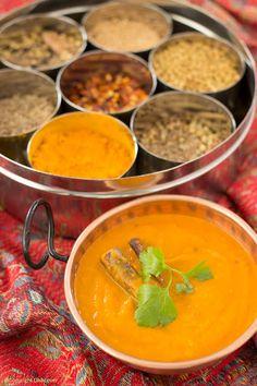 De Indiase keuken -  tomatencurry. Met olie om te bakken – 3 uien – 3 knoflookteentjes – 20 g vers geraspte gember – 1 eetlepel korianderzaadjes, gevijzeld – 1 eetlepel Madras kerriepoeder – 1 eetlepel paprikapoeder – 1 eetlepel kurkuma - 1 eetlepel gemalen komijn – ½ à 1 gedroogd pepertje, zonder zaadjes - 1 kaneelstokje – enkele kerrieblaadjes – 2 dl water + 1 groentebouillonblokje – 4 verse tomaten in blokjes - 1 theelepel garam masala - verse koriander – peper en zout naar smaak