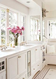 Love the clean bright white in this bathroom. Sometimes white can be boring but here with pops of color from the flowers and the sun shining in from the large bathrooms makes it a great place to take a long relaxing bubble bath. - bhg.com