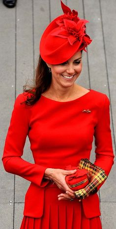 The Duchess of Cambridge wore a birght red dress and clutched a small red bag and Strathearn tartan scarf.
