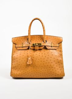 """This luxurious 35cm size Birkin handbag is a warm orange-tan """"Saffron"""" color. It features two rolled top handles and two front straps that secure with the gold toned turn lock closure. A matching leat"""