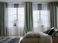 A bright bedroom featuring mullion windows with black black-out roller blinds, one layer of sheer white curtains that filters the daylight and one layer of grey-green thick curtains for privacy.