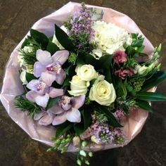 A subtle bouquet of white, pink and purple flowers highlighted with purple Cymbidium Orchids and foliages.  Part of Mothers Day 2016 Collection.