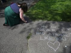 A woman adds her thoughts to the quotes and remembrances written on the sidewalk in memory of actor Robin Williams at the site of a scene in the movie 'Good Will Hunting' in the Public Garden in Boston, Massachusetts August 12, 2014.  REUTERS-Brian Snyder.  We aint never had a friend like you