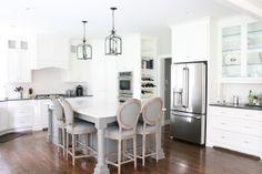 Pretty kitchen with white cabinetry, grey kitchen island & lantern light fixtures