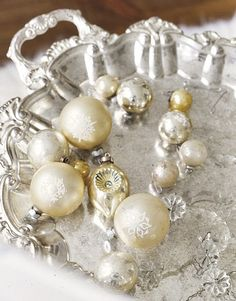Vintage Ornaments on a Tea Tray:   Silver loves white, so try displaying your vintage ornaments on a tea tray, like confections. Or enlist a silver candy dish or mercury-glass vase.  Photo Credit: Janis Nicolay