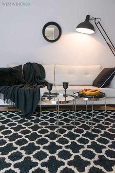 Die Farben der grafischen Prints auf dem Teppich spiegeln sich hervorragend im Sofa wider. Silberne Accessoires verleihen Räumen eine kühlere und maskulinere Note.