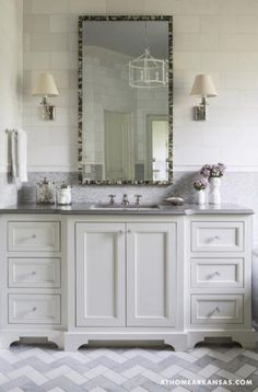 Down to Earth | At Home Arkansas. MH Design, Inc. Melissa Haynes Design, Master bathroom with Carrara marble mini-brick to the chair rail, Thasos marble above, and a Thasos-Carrara herringbone pattern on the floor. Custom, locally crafted sink cabinet with Quartz top. The Oly chandelier and mirror complete the space. Photo by Rett Peek.