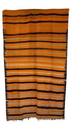 Use this great blanket to add some authentic Moroccan style to your home. This wool blanket features a tiger stripe palette of orange, black and gold, with an eye catching tribal detail around the border. Some fraying on one end. Can be used as a blanket, carpet, or table covering. Available at Maryam Montague's online Souk!