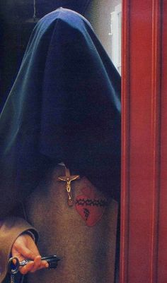 Religious Victims of the Sacred Heart of Jesus. Carmelite nun with veiled face. Before the Vatican II Council the trademark of Catholic nuns used to be their habit, consisting of flowing robes and veils that covered the entire body, leaving only the face and hands visible.