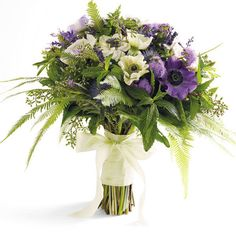Carry your luckwith you in a bouquet featuring lavender with white and purple anemones, ferns, salvia, eucalyptus, rosemary, thistle, ageratum, and mint. Bouquet byArtfool.