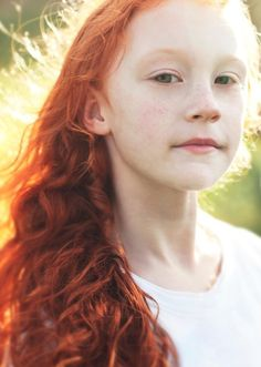 Beautiful redhaired young female with green eyes.