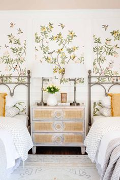 toddler girl room with twin beds, cane webbing dresser, chinoiserie wallpaper, and cottagecore bedding